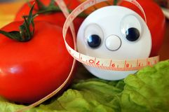 Wellness centimeter with eyes look on tomato and salad. Wellness and diet, tomato and helth centimeter, Red tomato and salad lettuce Royalty Free Stock Image