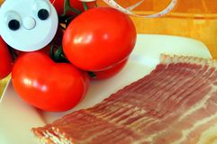 Wellness centimeter with tomato and becon. Wellness centimeter with eyes look from tomato on becon Stock Image
