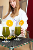 Wellness - Chlorophyll-Shake on a table. Chlorophyll-Shake in spa are on table, a woman takes the drink Stock Photo