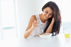 Wellness concept. Woman eating cereal and smiling. Healthy break. Wellness concept. Beautiful young woman eating organic cereal and smiling. Healthy breakfast in Royalty Free Stock Photo