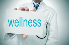 Wellness. A doctor showing a signboard with the word wellness written in it Royalty Free Stock Photography