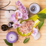 Wellness environment with essential oils, orchid and bath salts. Spa.Composition with orchid flowers, some small bottles with essential oil, pink salts, candles stock photography