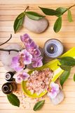 Wellness environment with essential oils, orchid and bath salts. Spa.Composition with orchid flowers, some small bottles with essential oil, pink salts, candles royalty free stock photography