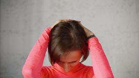 Woman puts hands on back of head and tilts head forward stretching neck muscles. Wellness exercise for cervical osteochondrosis. Woman puts hands on back of her stock footage