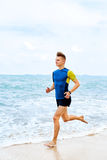 Wellness. Fit Athletic Man Running On Beach,Jogging During Worko Stock Photography