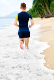 Wellness. Fit Athletic Man Running On Beach,Jogging During Worko Royalty Free Stock Photography