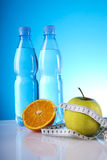 Wellness food and diet. Bottles of mineral water with fruits and measuring tape Stock Photography