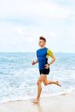 wellness Funzionamento atletico adatto dell'uomo sulla spiaggia, pareggiante durante il Worko Fotografia Stock