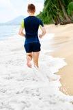 wellness Funzionamento atletico adatto dell'uomo sulla spiaggia, pareggiante durante il Worko Fotografia Stock Libera da Diritti