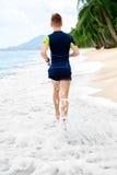 wellness Geeigneter athletischer Mann, der auf dem Strand, rüttelnd während Worko läuft Stockfotos