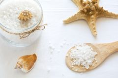 Wellness het plaatsen Overzees zout in glas, zeep, handdoek, olijfolie en bloemen op witte geweven achtergrond Royalty-vrije Stock Foto
