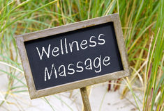 Wellness Massage. Chalkboard or blackboard with text and sand or beach and green grass in the background Stock Images