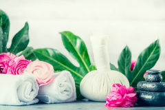 Wellness or massage setting with hot stones , towels,flowers, herbal ball and palm leaves for spa treatment Royalty Free Stock Photo