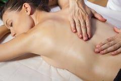 Wellness. Masseur doing massage on woman body in the spa salon. Stock Image