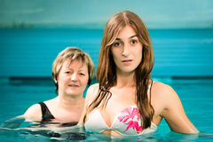 Wellness - mature and young woman in swimming pool royalty free stock photos