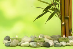 Wellness motive with bamboo and candles. In green Royalty Free Stock Photography