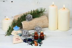 Winter spa concept with candles. Wellness objects, aromatic herbs, anti stress bath crystals and essential oil on white wood table Royalty Free Stock Photography