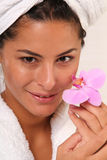 Wellness with a Orchid. Beautiful brunette woman holding a pink orchid stock photos