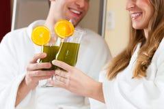 Wellness - Paar mit Chlorophyll-Erschütterung im Badekurort lizenzfreie stockfotografie