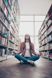 Wellness, peace, chill, rest, wisdom, education, campus lifestyle. Low angle shot of young calm nerdy girl, practicing yoga in th. E lotus position on wooden stock photography