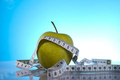 Wellness products. Green apple and measuring tape Stock Photos