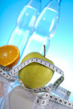 Wellness products. Green apple with orange and measuring tape Stock Image