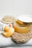 Wellness, rubber duck, pumice stone, hairbursh and glove on a white towel Stock Photos