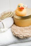 Wellness, rubber duck, pumice stone, hairbursh and glove on a white towel Stock Photography