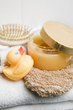 Wellness, rubber duck, pumice stone, hairbursh and glove on a white towel Royalty Free Stock Photos