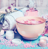 Wellness setting with orchid flowers floating in bowl of water with spa and cosmetic tools. Vertical composing. Pastel toned Royalty Free Stock Photos