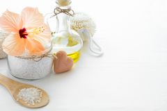 Wellness setting. Sea salt in glass, soap, towel, olive oil and flowers Royalty Free Stock Photo