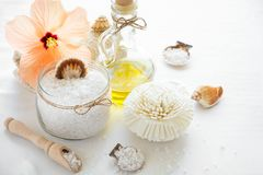 Wellness setting. Sea salt in glass, soap, towel, olive oil and flowers Stock Photos