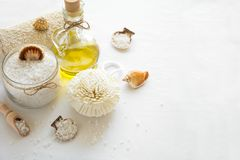 Wellness setting. Sea salt in glass, soap, towel, olive oil and flowers on white textured background Stock Image