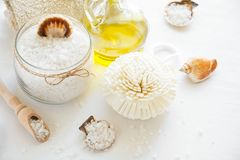 Wellness setting. Sea salt in glass, soap, towel, olive oil and flowers on white textured background Stock Photo