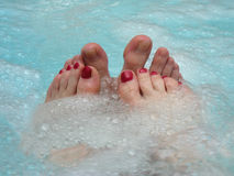 Wellness & Spa. Two female and two male feet in the turqoise water of a whirlpool Stock Image