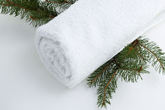 Wellness spa. White spa towel rolled on white background with pine branches Royalty Free Stock Photos