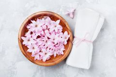 Wellness and spa composition of perfumed pink flowers water in wooden bowl and terry towel on gray stone table. Aromatherapy. Wellness and spa composition of Royalty Free Stock Photography