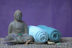 Wellness and spa concept. Wellness and spa atmosphere with buddha, towels, lavender and stones in lila and green colors stock photography