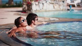 Wellness Spa couple relaxing in swimming pool outdoor at luxury resort spa retreat. Happy young woman and man in. Sunglasses relaxed resting on travel vacation stock video