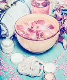 Wellness or spa setting with water bowl with flowers, cream, towel and bath tools. Pastel color toned royalty free stock photos