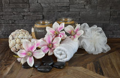 Wellness still life concept. Spa still life with hot stones, towel, Magnolia flowers, candle light and decoration ball with sea shells on rustic wooden table Royalty Free Stock Photography