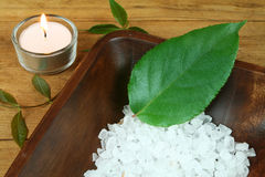 Wellness therapy. Spa still life - salt crystals and green leaf in wooden bowl Royalty Free Stock Image