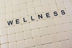 Wellness In Tiles. Tiles with letters spell out the word 'wellness' in the middle of blank tiles Royalty Free Stock Image
