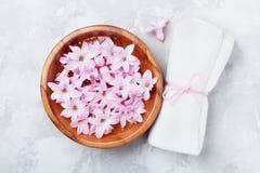 Wellness und Badekurortzusammensetzung von parfümierten rosa Blumen wässern in der hölzernen Schüssel und im Frotteestoff auf gra lizenzfreie stockfotografie