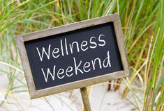 Wellness Weekend - chalkboard with text at the beach. Wellness Weekend - wooden chalkboard with text at the beach stock photography