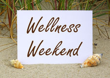 Wellness Weekend sign on beach. With shells in foreground royalty free stock images