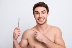 Wellness, wellbeing concept - neat, attractive, joyful, cheerful. Sexy macho, shirtless,  sporty guy, muscular model, gesture effective teeth brush with Stock Photo