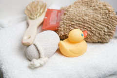 Wellness, white towel with pumice stone, hairbrush, rubber duck Stock Photography