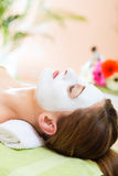 Wellness - woman getting face mask in spa. Wellness - woman receiving facial mask in spa for clean and moist skin Royalty Free Stock Photography