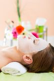 Wellness - woman getting face mask in spa. Wellness - woman receiving facial mask in spa for clean skin royalty free stock images